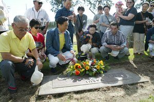 Mayor Kenji Nakano, center left, prays with other Tsuruta citizens in 2002 at the gravesite of Sister City founder Chop Yasui.