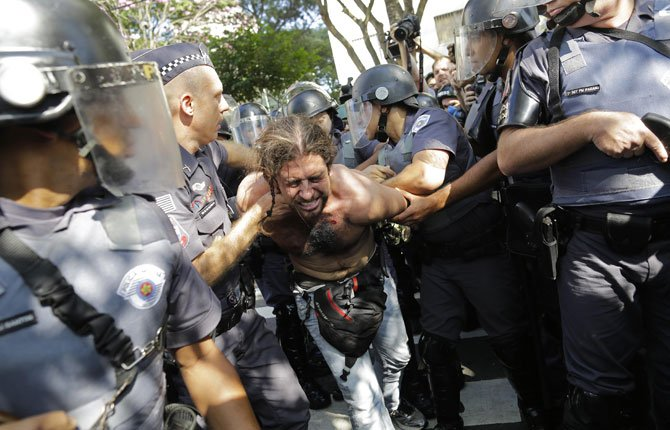 A protester is detained by police during a demonstration by people demanding better public services and against the money spent on the World Cup soccer tournament June 12 in Sao Paulo, Brazil. Brazilian police clashed with anti-World Cup protesters trying to block part of the main highway leading to the stadium that hosts the opening match of the tournament.
