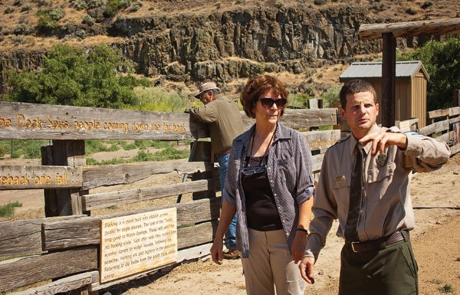 MARY MACNAB and Park Ranger David Spangler talk about research done to create signboards on an interpretive fence line at Cottonwood Canyon State Park near Wasco while Mary's husband Bo, back, checks out the stability of the display.