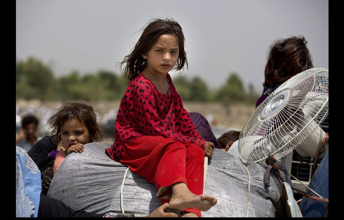 Pakistani tribal people arrive in Bannu, Pakistan, Wednesday, June 18. Thousands of villagers fled as Pakistani army relax a curfew in troubled North Waziristan. Pakistani jets pounded targets in the country's northwest in major offensives designed to root out safe havens in the volatile region.