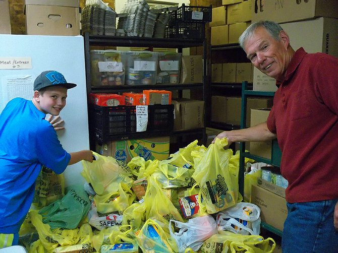 Odell Lion Chuck Bugge and his grandson, Jesse Wilson, unload donated food at the FISH food bank.