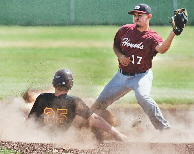 Sunnyside Christian base runner Ryan Roedel creates a cloud of dust with his slide into second base in Monday's opening game against the Grandview Greyhounds' summer baseball team.