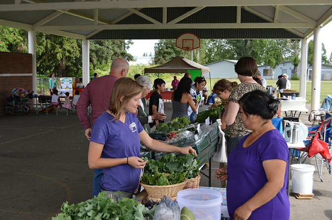 El Mercado del Valle Market Manager Anna Osborn chats with Next Door's Isabel Sanchez, who was manning the community table at Saturday's market. Community members are encouraged to bring extra garden produce to sell at the booth.