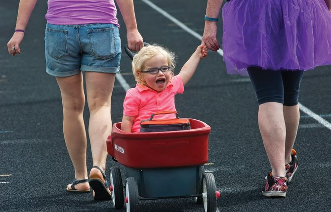 GAVIN ADAMS, 2, laughs with joy as he is drawn down the track at the Wahtonka campus by his mother Brandi Adams, left, and Cindi Vipperman during Relay for Life Saturday, June 21. They were walking for the Fred Meyer relay team.