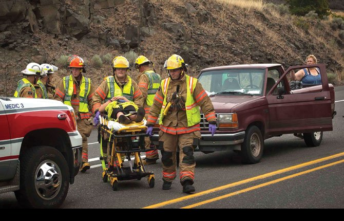 AN INJURED passenger is transported by Mid-Columbia Fire and Rescue medics to an ambulance Wednesday afternoon following a two-vehicle accident in which the vehicle she was riding in was rear-ended while stopped for road construction at the intersection of Highway 197 and Highway 30 east of The Dalles. Both vehicles remained drivable and were soon cleared.
