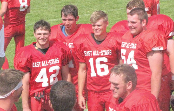 Sherman's Nick Coleman, middle, is flanked by Dufur all-state winners Cole Parke (42) and Austin Olson (54) moments before taking the field for the East squad last weekend for the Eight-Man All-Star Football game in La Grande. 	  	                        	Contributed photo