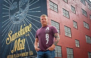ARTIST JIM SEMLOR stands in front of one of two Sunshine Mill murals he designed to help make the historic landmark a marquee destination winery. The graphics of the mural will be reflected in all of the marketing materials for the mill, as one version of the logo suggests.