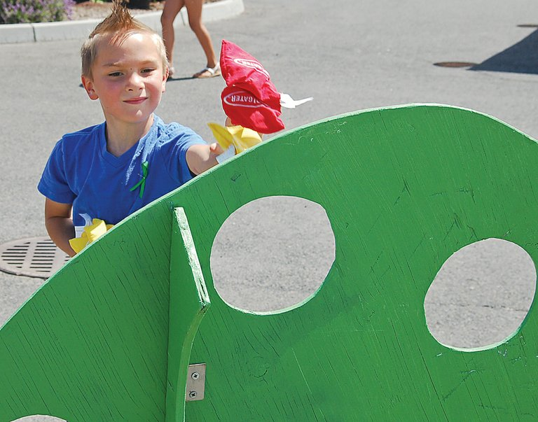 Aidan Marquez throws beanbags through a kidney-shaped cornhole board. The event featured basketball games and face painting for children along with plenty of educational booths.