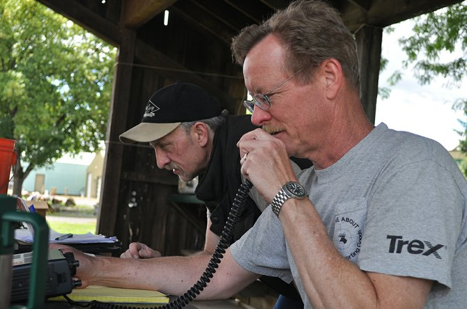 Dialing in a frequency to make contact with other amateur radio operators last Saturday, June 28, were (front) Brian Davis of Kooskia and (back) James Cox of Grangeville.