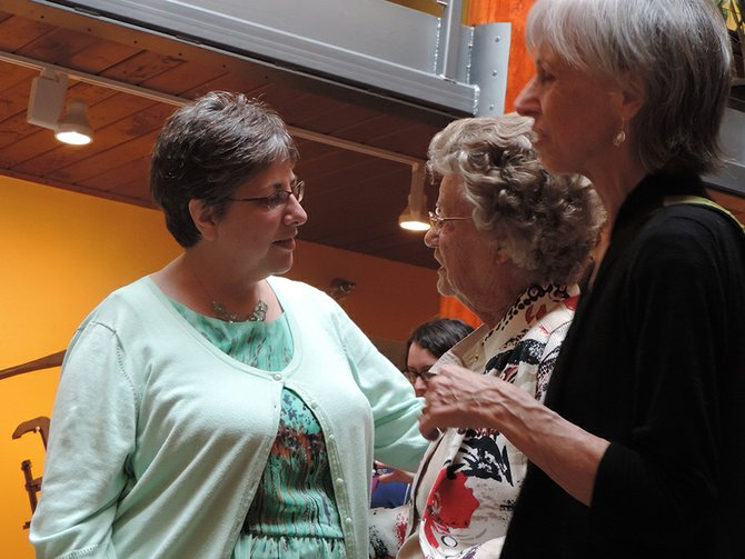 Friends greet Connie Nice, left, in the museum atrium during Monday's reception. Nice, recovering from shoulder surgery, said that for her next chapter she is looking at picking up past projects, including a children's book manuscript.