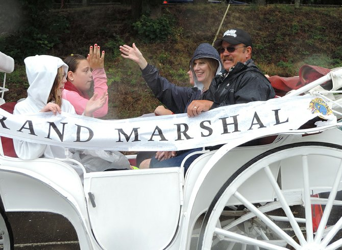 Grand marshal Kari Goben waves along with her family.