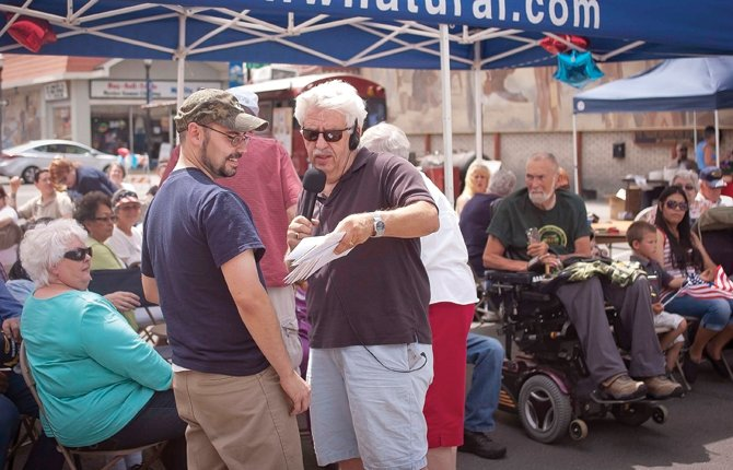 Al WYN, owner of KODL Radio in The Dalles, hands out a certificate of appreciation and gift card for services to veteran David McGaughey at the Hometown Heroes segment of Fourth of July festivities. Mona Fox, operations manager, said the broadcast center wanted to honor the men and women who had defended America's freedoms during the Independence Day celebration. She said local merchants came foward with generous donations for the 15 veterans who were present to accept awards, along with their families.	Mark B. Gibson photo