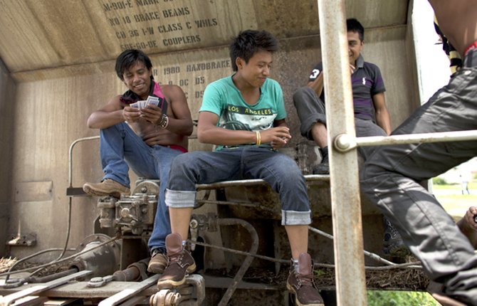 young Central American migrants traveling together play cards on a parked boxcar as they wait for a northbound freight train at the station in Arriaga, Chiapas state, Mexico on June 19. AP Photo/Rebecca Blackwell