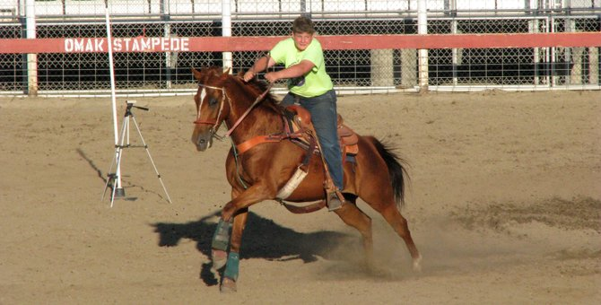 Braden Hennigs competes in barrels on his horse, Song, on Wednesday in the Omak Stampede Arena.