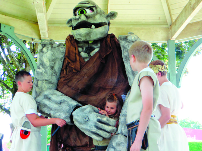 The Cyclops grabs Antitheses, played by Fiona Harriman, 8, to eat her after discovering Odysseus, played by Chase Magill, 12, (front) and his Greek soldiers in the monster's cave. The Cyclops, on loan from Portland Community College, is puppeteered by Scott McCannell of Monmouth. It requires three people to make it work, and includes an eye that blinks and mouth that talks.