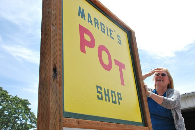 Margie Lemberger unveiled the sign for her new recreational marijuana shop in Bingen last week. As of Monday, Margie's Pot Shop became one of 24 legally licensed marijuana retailers in the State of Washington, though shortages in product have stalled business.
