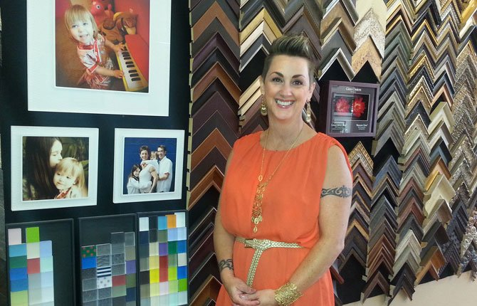 Marty Hiser of Westwind Frame & Gallery celebrates her silver anniversary in the framing trade this year. She is pictured with photos of her family, which plays a big role in her business, and the chevron-patterned framing materials display that makes up an entire wall of her business.