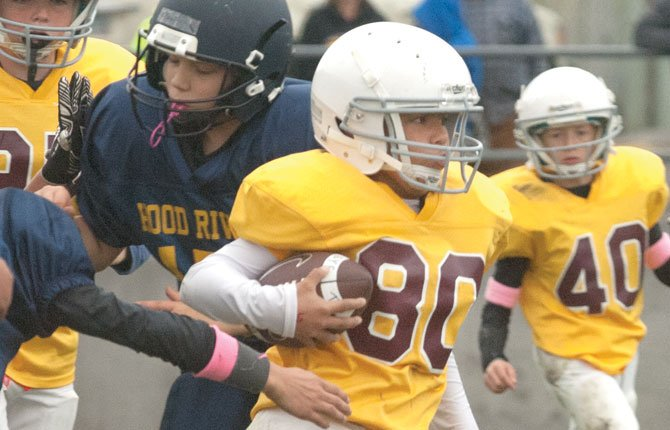 YOUTH FOOTBALL back Al Gallegos scurries through a hole for some big yardage in The Dalles Youth Football play in The Dalles. The organization has its signups from July 21-24 at Amaton Field.