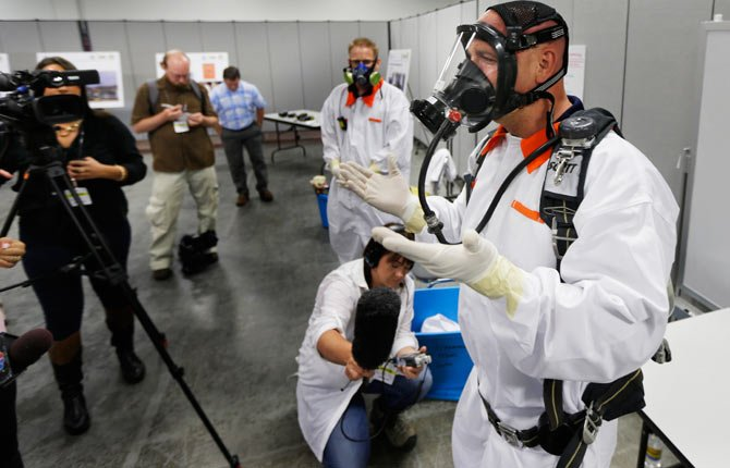 Bob Wilkinson, right, an environmental safety manager for the contractor Washington River Protection Solutions, demonstrates protective and clothing and a scuba-type tank-and-mask breathing apparatus used by workers in areas with potential exposure to possibly harmful vapors during a media tour of the Hanford Nuclear Reservation Wednesday, July 9, 2014 near Richland, Wash. Officials said Wednesday that 12,000 air samples taken at Hanford this year after more than three dozen workers reported being sickened by chemical vapors have failed to find a cause for the problem.
