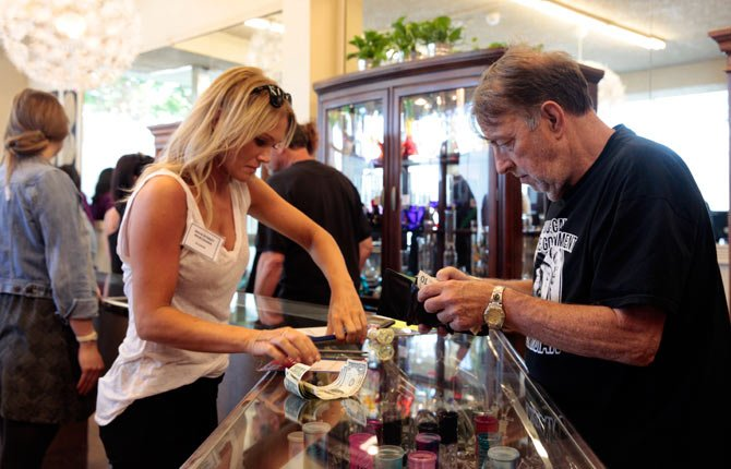 At Main Street Marijuana in Vancouver, Wash., a customer buys marijuana on the first day of sales at the store, Wednesday, July 9, 2014. The southwest Washington city is just a 10-mile drive from downtown Portland, Ore.