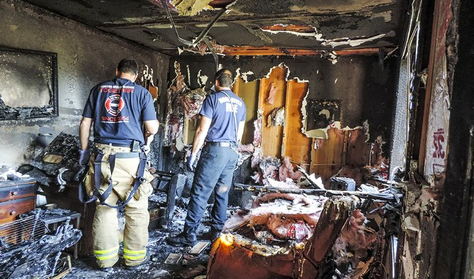 HOOD RIVER Fire Department captains Dave Smith, left, and Clayton McRea investigate the Indian Creek Apartment fire on Friday morning.