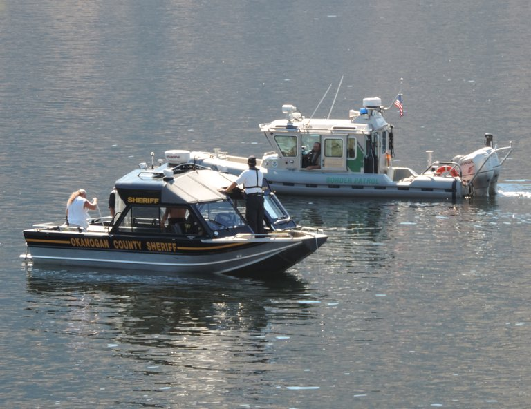 Okanogan County Sheriff's Office and U.S. Border Patrol boats comb the water of Palmer Lake late Friday in an attempt to locate the body of a swimmer who is missing and presumed drowned.
