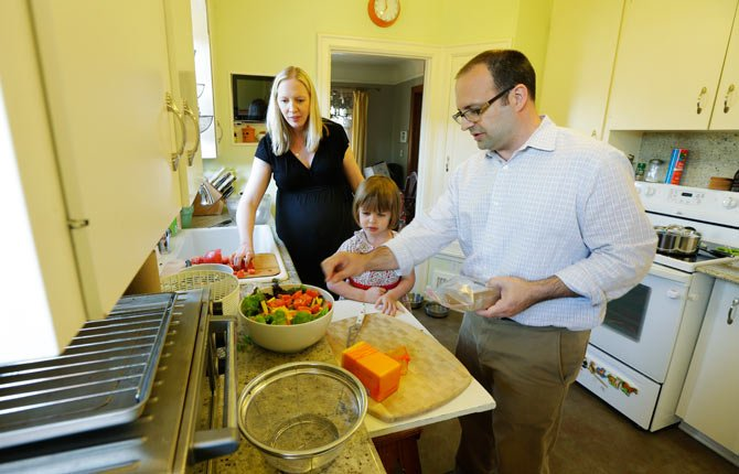 In this July 2, 2014 photo, Ryan Carson, right, cooks dinner with his wife, Jenny Roraback-Carson, left, and their daughter Clara, 3, at their home in Seattle. The Carsons are one of many would-be home sellers across the country who have mortgage rates so low, it doesn't make financial sense to sell their homes, even if they need more space, a trend which limits the supply of homes and can contribute to slower home sales.