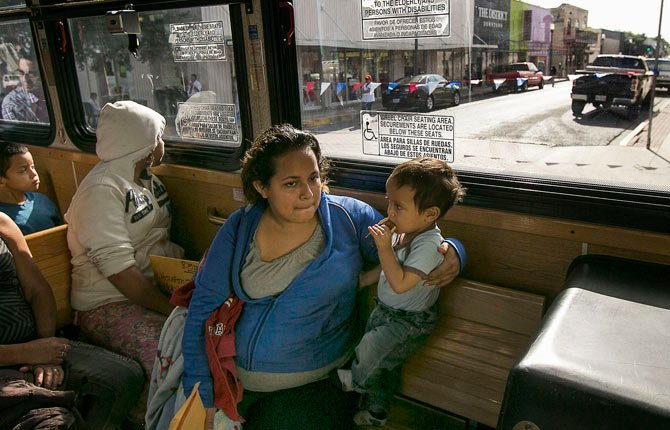In this photo taken July 4, 2014, Marta Beltran, 19, of El Salvador, holds her 18-month-old son, Lenny, as they ride a city shuttle bus from the McAllen city bus station to the Sacred Heart Catholic Church Shelter in McAllen, Texas. About 90 Hondurans a day cross illegally from Mexico into the U.S. at the Rio Grande near McAllen, according to the Honduran Consulate, and the families are then brought to Central Station in McAllen and each is released on their own recognizance. Though most travelers have enough money to purchase their own bus tickets to meet family in cities across the U.S., many have nowhere to stay before the buses leave, and most are in need of rest, medical attention and sustenance. It falls to the local government and charities to welcome the uninvited visitors to America. Tens of thousands have also fled to the U.S. from El Salvador and Guatemala to escape violence.