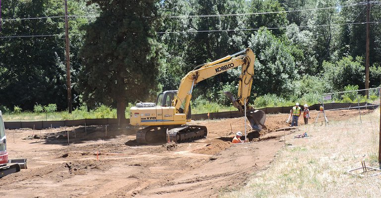 A CRESTLINE crew begins excavation for sewer lift line project, in the open field on Union next to the Pacific Power substation; Indian Creek trail, along the fence line in background, remains open.