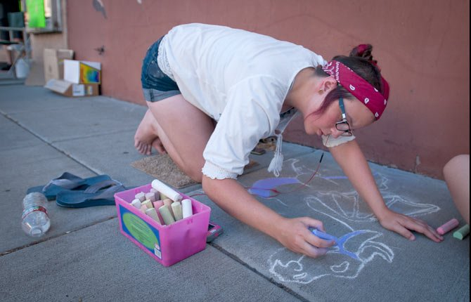 Dorothy Young, 15, works on a chalk drawing at the Jammin' July Street Festival Saturday, July 11.