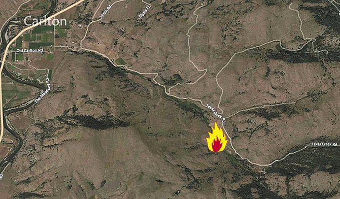 The flame icon shows the approximately location of the Texas Creek Road wildfire reported Monday east of Carlton.