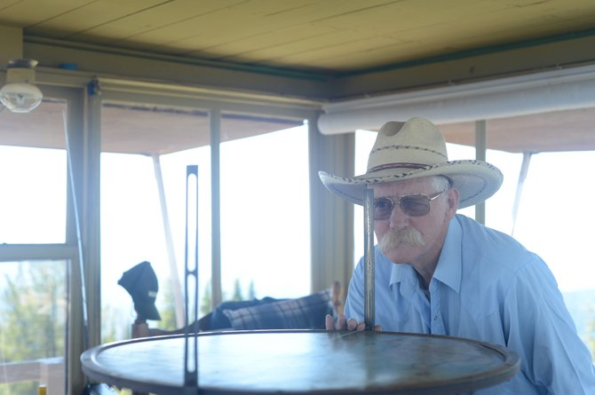 "Pilot Knob lookout Gary Dutcher demonstrates the use of what he calls ""the most primitive fire-finder ever."""