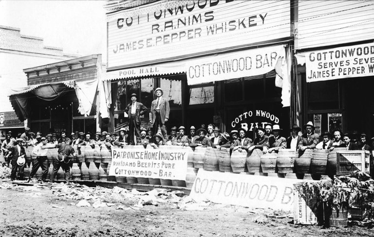 Men and kegs of beer outside the Cottonwood R. A. Nims James E. Pepper Whiskey Bar during a Fourth of July celebration, 1913.