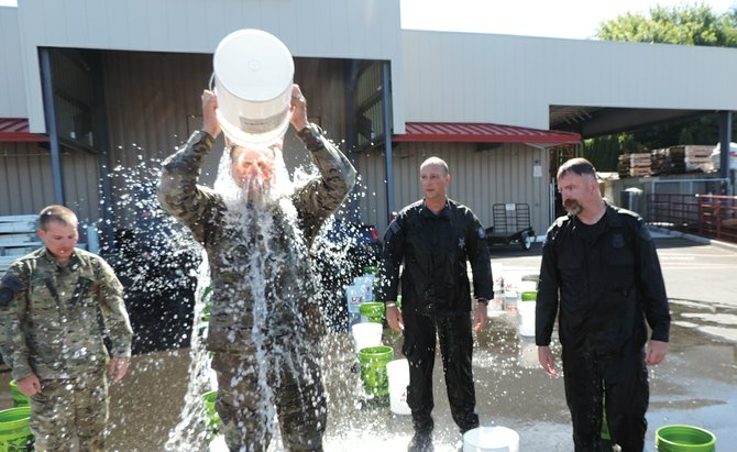 BUCKET LIST with a new meaning: Zach Bohince, left, Gavin McIlvenna and Kris Barber stand by as Andrew Vanderwerf pours a bucket of ice water over his head in the parking lot of Hood River Supply, which provided the buckets and water. On the warm Friday morning, working mostly in the shade, the four law enforcement officers stood and delivered, calling the names of the fallen as each new five-gallon dose cascaded. Below are McIlvenna, Bohince, Barber and Vanderwerf. All are Hood River residents; Barber works for Portland Police Bureau and the others are Oregon State troopers.