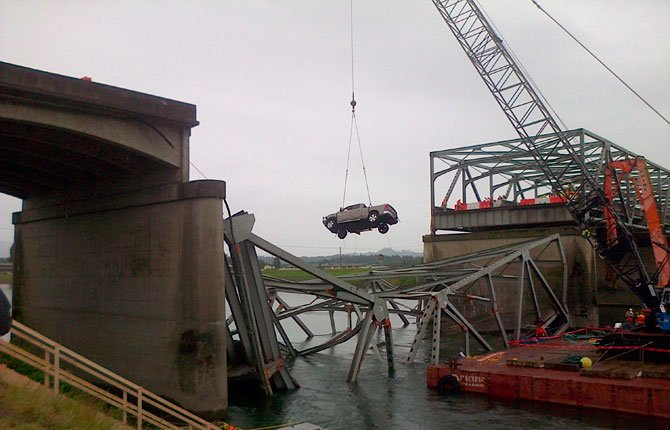 A crane removes a pickup truck from the wreckage of the Interstate 5 bridge over the Skagit River in Mount Vernon, Wash. Metal fatigue is evident in a steel truss bridge over Interstate 5 in Washington state, south of this similar steel truss that collapsed May 23, 2013.