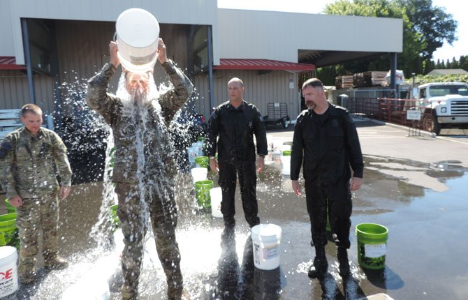 BUCKET LIST with a new meaning: Zach Bohince, left, Andrew Vanderwerf and Kris Barber stand by as Gavin McIlvenna pours a bucket of ice water over his head in the parking lot of Hood River Supply, which provided the buckets and water for the Cold Water Challenge that honored Oregon State Police officers and others who died in the line of duty.