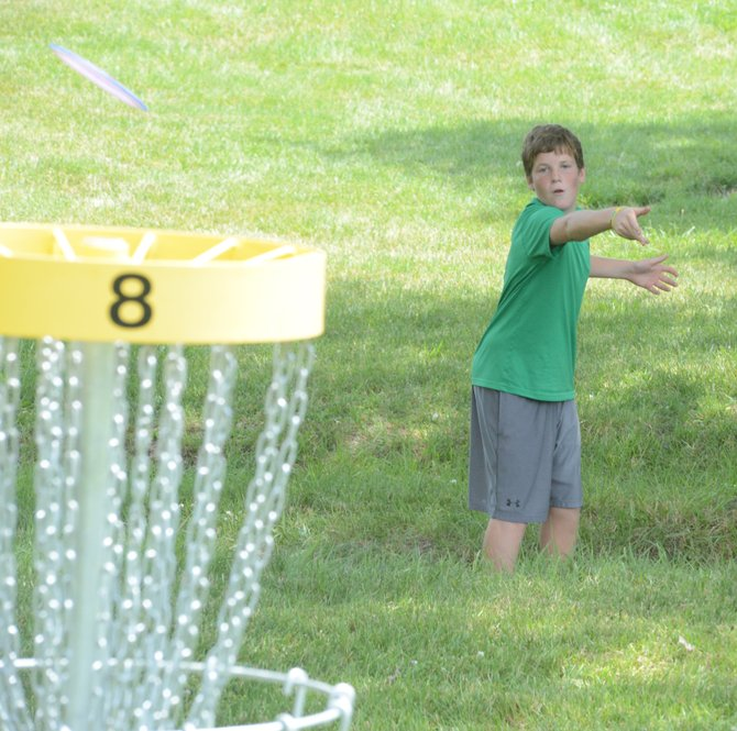 Dawson Palm, visiting his Krogh and Frei cousins who live in the Grangeville area, finishes No. 8 on the Lions Park disc golf course with a flourish.