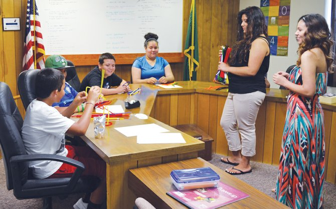 STEAM instructors Vanessa Sanchez and Yarelly Gomez (far right) guide middle schoolers through an engineering challenge of creating stable structures using only pipe cleaners. Students pictured from left are Nathan Gomez, Tony Meza, Freddy Macedo and Felicia McDaniel. Not pictured: Rudy Velasquez. The program is temporarily being held in Mabton City Council chambers, until work wraps up on a former church building the city owns near Feezel Park.