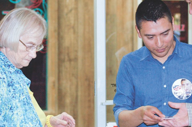 Supporter Barbara Merz of Sunnyside speaks with political newcomer Estakio Beltran as he passes out a campaign button at the candidates forum held Wednesday night at Sunnyside's Conquistador Restaurant. Beltran, a candidate for the Fourth Congressional District seat being vacated by Rep. Doc Hastings, was one of four candidates who were in Sunnyside drumming up support for their political ambitions.