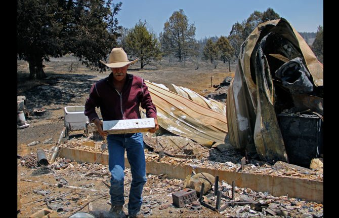Sprague River, Ore., resident David Pool lifts a marble block from the rubble left by the Moccasin Fire, Tuesday, July 15, 2014. The stone, which came from the hospital where his oldest son was born, is one of the few items at his home not destroyed by the blaze.
