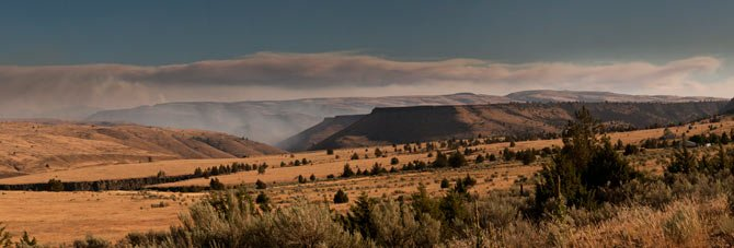 Light blue smoke, center, marks nearby burns in the Maupin area of the Deschutes River Canyon in this panorama created from multiple exposures. The long fire cloud in the background is from the Shaniko Butte Fire complex, which Maupin area fires are a part of.