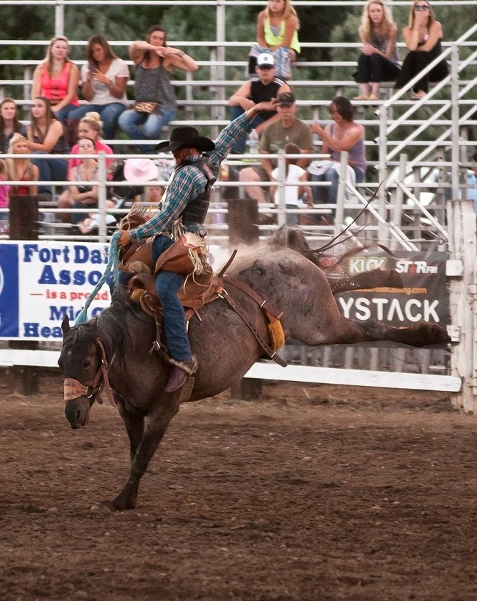 Cash Casey of Madras competes in saddle bronc riding competition at the Rough and Wild Fort Dalles Rodeo Thursday night.