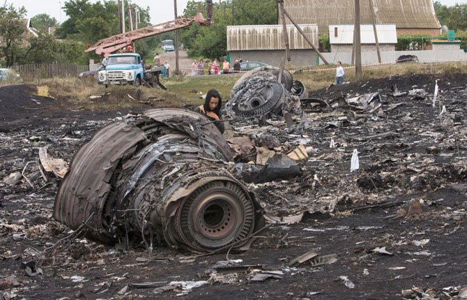 A woman walks at the site of a crashed Malaysia Airlines passenger plane near the village of Rozsypne, eastern Ukraine Friday, July 18. Rescue workers, policemen and even off-duty coal miners were combing a sprawling area in eastern Ukraine near the Russian border where the Malaysian plane ended up in burning pieces Thursday, killing all 298 aboard.