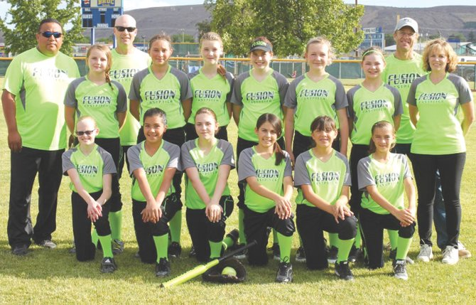 The 2014 12U Fusion fastpitch team includes (back row L-R) Coach Miguel Puente, Reyann Baker, Coach Jim Gauley, Bella Arriaga, Erin Gauley, Anna Nordstrom, Eve Rice, Samantha Norem, Keith Spencer and Mari Spencer; (front row L-R) Taylor Spencer, Olivia Puente, Sevyn Corbin, Essence Cazares, Angelique Madrigal and Kaycee Hazzard.