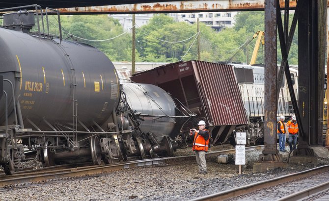 An investigator photographs the scene where a locomotive and cars carrying crude oil went off the track beneath the Magnolia Bridge in the Interbay neighborhood of Seattle, Thursday morning, July 24, 2014.