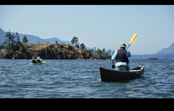 WOODED ISLANDS, some only visible from the water, dot the landscape of the central Columbia Gorge. Ole Helgerson, a seasoned oarsman, paddles a canoe on the main Columbia River, despite a bit of wind-driven chop.
