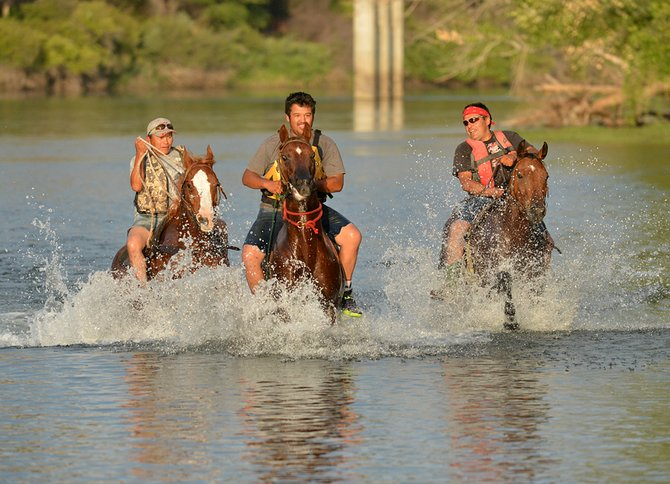 World-Famous Suicide Race outriders enjoy a splash in the Okanogan River on Sunday. They included, from left, Gary Sam, Phillip Williams and Bass Williams. Practice concludes Friday and Saturday.