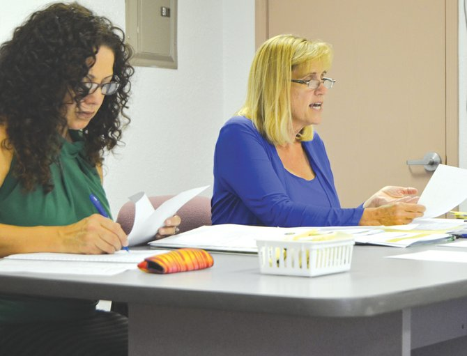 Mabton School District Finance Director Gina Grow (right) explains the proposed 2014-15 budget at Monday's school board meeting as Administrative Secretary Ruth Villanueva looks through the figures.