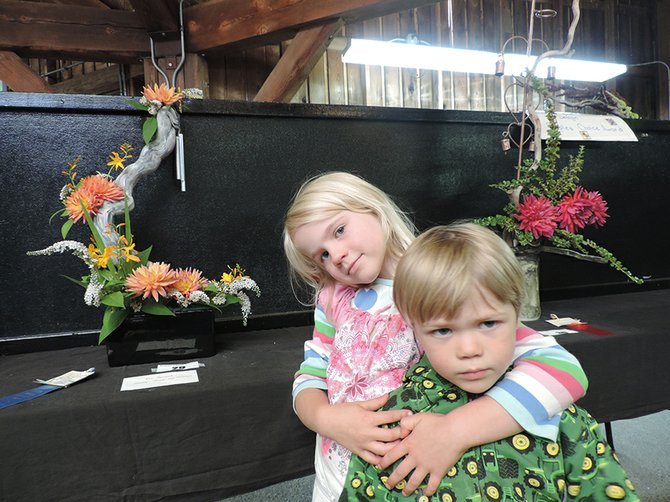 "Anaka Diem, 5, with her brother, Forrest, 3, stands with her Horticulture People's Choice selection on Thursday. The arrangement by Margaret Taylor of Hood River just happened to be voted People's Choice winner, it was announced on Saturday. Besides being beautiful, the arrangement was interactive; the floral displays are typically ""hands-off,"" but Margaret attached a sign that read ""For sound, gently touch chimes,"" which Anaka demonstrated."