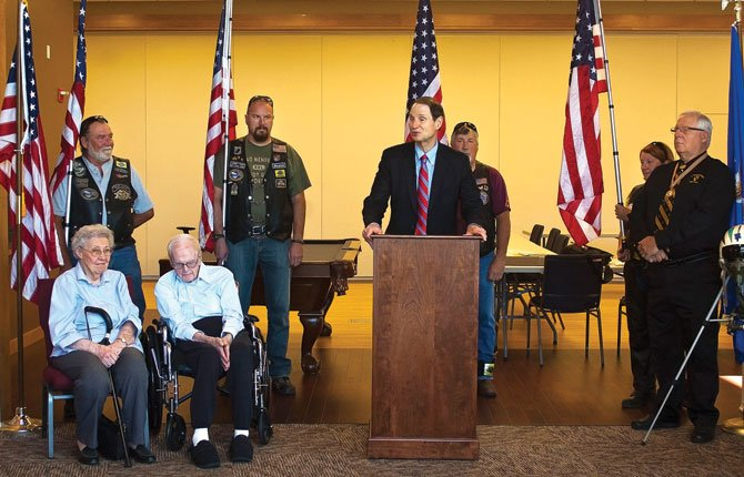 U.S. SEN. RON WYDEN, flanked by members of the Patriot Guard Riders, prepares to award USAF Lt. Colonel George Ruddell, seated with his wife Mavis, with the Congressional Gold Medal during a ceremony at the Oregon Veterans Home in The Dalles July 26.